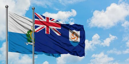 San Marino and Anguilla flag waving in the wind against white cloudy blue sky together. Diplomacy concept, international relations.