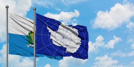 San Marino and Antarctica flag waving in the wind against white cloudy blue sky together. Diplomacy concept, international relations.