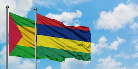Sao Tome And Principe and Mauritius flag waving in the wind against white cloudy blue sky together. Diplomacy concept, international relations.