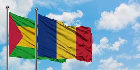 Sao Tome And Principe and Romania flag waving in the wind against white cloudy blue sky together. Diplomacy concept, international relations.