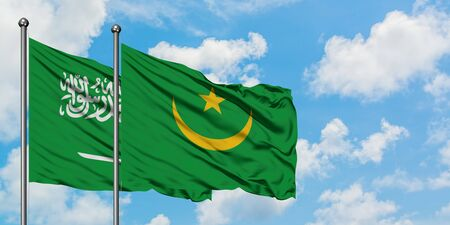 Saudi Arabia and Mauritania flag waving in the wind against white cloudy blue sky together. Diplomacy concept, international relations. Фото со стока