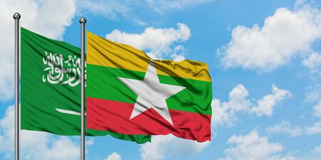 Saudi Arabia and Myanmar flag waving in the wind against white cloudy blue sky together. Diplomacy concept, international relations.