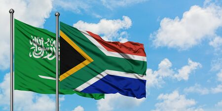 Saudi Arabia and South Africa flag waving in the wind against white cloudy blue sky together. Diplomacy concept, international relations.