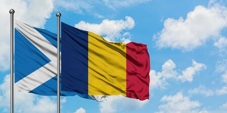Scotland and Chad flag waving in the wind against white cloudy blue sky together. Diplomacy concept, international relations. Archivio Fotografico