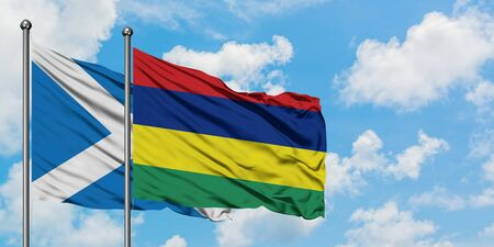 Scotland and Mauritius flag waving in the wind against white cloudy blue sky together. Diplomacy concept, international relations. Stock fotó