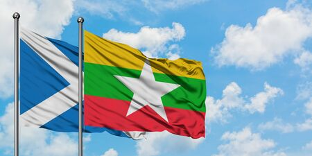 Scotland and Myanmar flag waving in the wind against white cloudy blue sky together. Diplomacy concept, international relations.