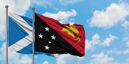Scotland and Papua New Guinea flag waving in the wind against white cloudy blue sky together. Diplomacy concept, international relations.