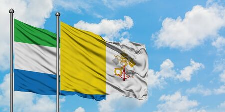 Sierra Leone and Vatican City flag waving in the wind against white cloudy blue sky together. Diplomacy concept, international relations.