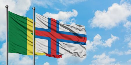 Senegal and Faroe Islands flag waving in the wind against white cloudy blue sky together. Diplomacy concept, international relations.