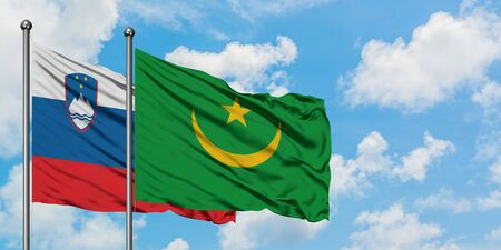 Slovenia and Mauritania flag waving in the wind against white cloudy blue sky together. Diplomacy concept, international relations.