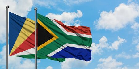 Seychelles and South Africa flag waving in the wind against white cloudy blue sky together. Diplomacy concept, international relations.