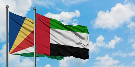 Seychelles and United Arab Emirates flag waving in the wind against white cloudy blue sky together. Diplomacy concept, international relations. Фото со стока