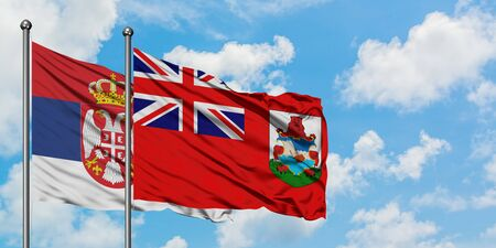 Serbia and Bermuda flag waving in the wind against white cloudy blue sky together. Diplomacy concept, international relations. Imagens