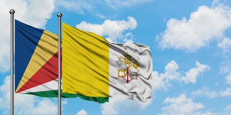 Seychelles and Vatican City flag waving in the wind against white cloudy blue sky together. Diplomacy concept, international relations.