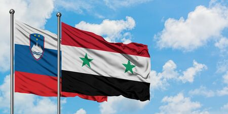 Slovenia and Syria flag waving in the wind against white cloudy blue sky together. Diplomacy concept, international relations.
