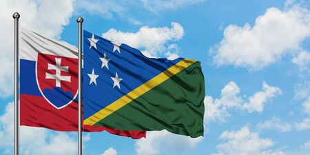 Slovakia and Solomon Islands flag waving in the wind against white cloudy blue sky together. Diplomacy concept, international relations.