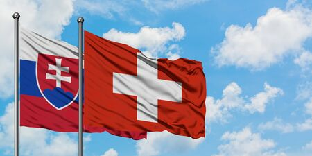 Slovakia and Switzerland flag waving in the wind against white cloudy blue sky together. Diplomacy concept, international relations.