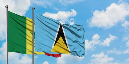 Senegal and Saint Lucia flag waving in the wind against white cloudy blue sky together. Diplomacy concept, international relations.