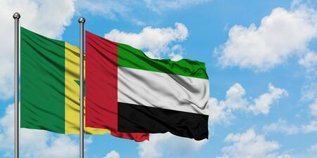 Senegal and United Arab Emirates flag waving in the wind against white cloudy blue sky together. Diplomacy concept, international relations. Фото со стока