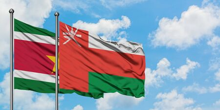 Suriname and Oman flag waving in the wind against white cloudy blue sky together. Diplomacy concept, international relations. Stockfoto