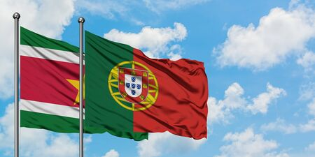 Suriname and Portugal flag waving in the wind against white cloudy blue sky together. Diplomacy concept, international relations. Stockfoto