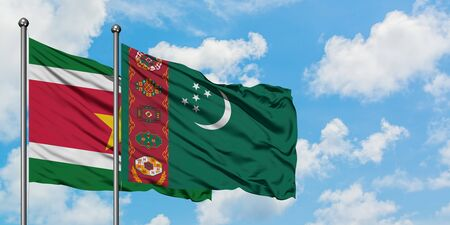 Suriname and Turkmenistan flag waving in the wind against white cloudy blue sky together. Diplomacy concept, international relations.