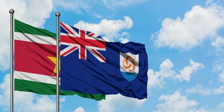 Suriname and Anguilla flag waving in the wind against white cloudy blue sky together. Diplomacy concept, international relations.