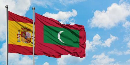 Spain and Maldives flag waving in the wind against white cloudy blue sky together. Diplomacy concept, international relations.