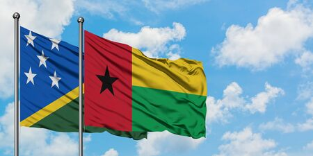 Solomon Islands and Guinea Bissau flag waving in the wind against white cloudy blue sky together. Diplomacy concept, international relations.