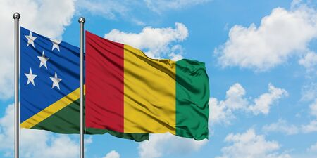 Solomon Islands and Guinea flag waving in the wind against white cloudy blue sky together. Diplomacy concept, international relations.