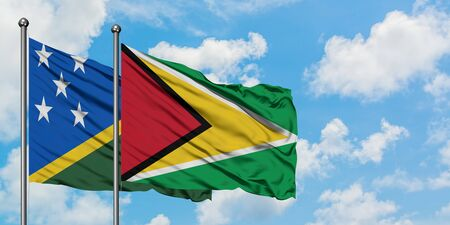 Solomon Islands and Guyana flag waving in the wind against white cloudy blue sky together. Diplomacy concept, international relations.