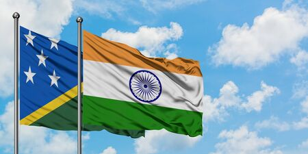 Solomon Islands and India flag waving in the wind against white cloudy blue sky together. Diplomacy concept, international relations.