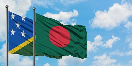 Solomon Islands and Bangladesh flag waving in the wind against white cloudy blue sky together. Diplomacy concept, international relations.