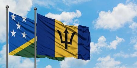 Solomon Islands and Barbados flag waving in the wind against white cloudy blue sky together. Diplomacy concept, international relations. Stok Fotoğraf