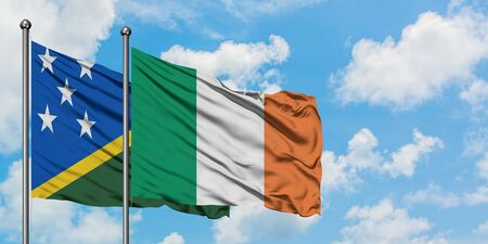 Solomon Islands and Ireland flag waving in the wind against white cloudy blue sky together. Diplomacy concept, international relations. Stok Fotoğraf
