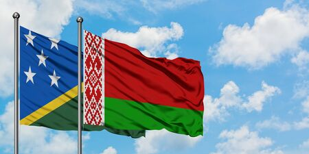 Solomon Islands and Belarus flag waving in the wind against white cloudy blue sky together. Diplomacy concept, international relations.