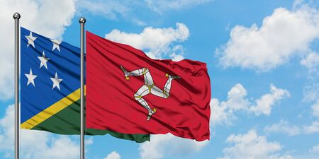 Solomon Islands and Isle Of Man flag waving in the wind against white cloudy blue sky together. Diplomacy concept, international relations.