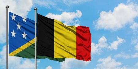 Solomon Islands and Belgium flag waving in the wind against white cloudy blue sky together. Diplomacy concept, international relations.