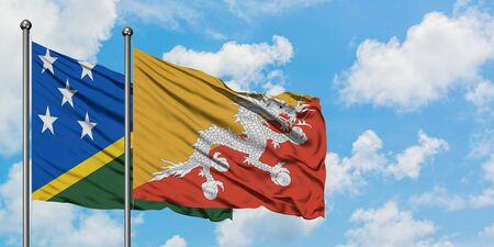 Solomon Islands and Bhutan flag waving in the wind against white cloudy blue sky together. Diplomacy concept, international relations.