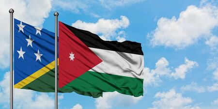 Solomon Islands and Jordan flag waving in the wind against white cloudy blue sky together. Diplomacy concept, international relations.