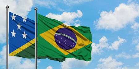 Solomon Islands and Brazil flag waving in the wind against white cloudy blue sky together. Diplomacy concept, international relations.