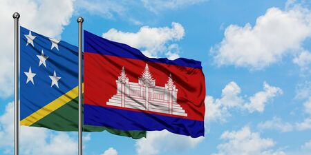 Solomon Islands and Cambodia flag waving in the wind against white cloudy blue sky together. Diplomacy concept, international relations.