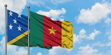 Solomon Islands and Cameroon flag waving in the wind against white cloudy blue sky together. Diplomacy concept, international relations.