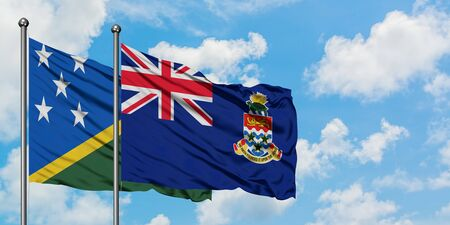 Solomon Islands and Cayman Islands flag waving in the wind against white cloudy blue sky together. Diplomacy concept, international relations.