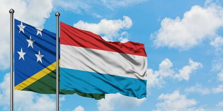 Solomon Islands and Luxembourg flag waving in the wind against white cloudy blue sky together. Diplomacy concept, international relations.