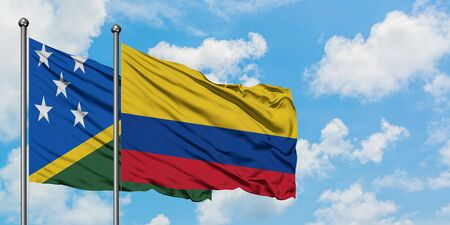 Solomon Islands and Colombia flag waving in the wind against white cloudy blue sky together. Diplomacy concept, international relations.