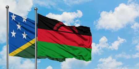 Solomon Islands and Malawi flag waving in the wind against white cloudy blue sky together. Diplomacy concept, international relations.