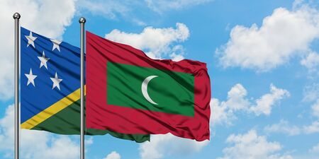 Solomon Islands and Maldives flag waving in the wind against white cloudy blue sky together. Diplomacy concept, international relations. Stok Fotoğraf