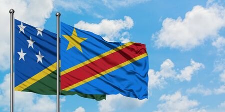 Solomon Islands and Congo flag waving in the wind against white cloudy blue sky together. Diplomacy concept, international relations.