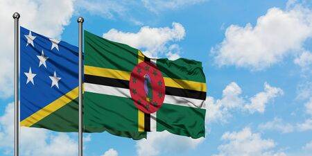 Solomon Islands and Dominica flag waving in the wind against white cloudy blue sky together. Diplomacy concept, international relations. Stok Fotoğraf